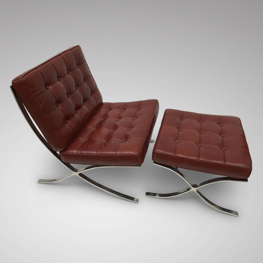 A MODERN LEATHER UPHOLSTERED CHAIR WITH MATCHING FOOTSTOOL