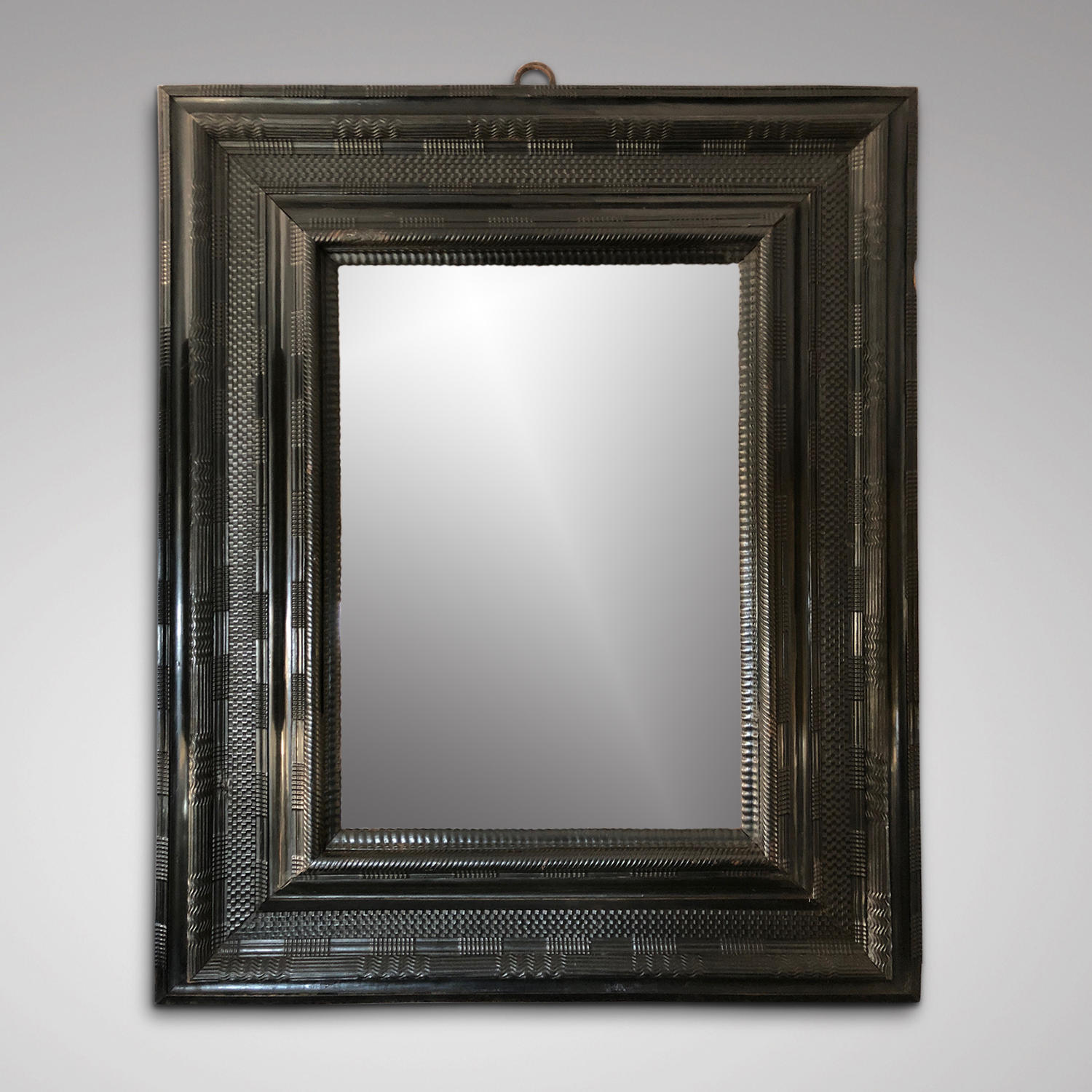A 17TH CENTURY EBONY CUSHION MIRROR